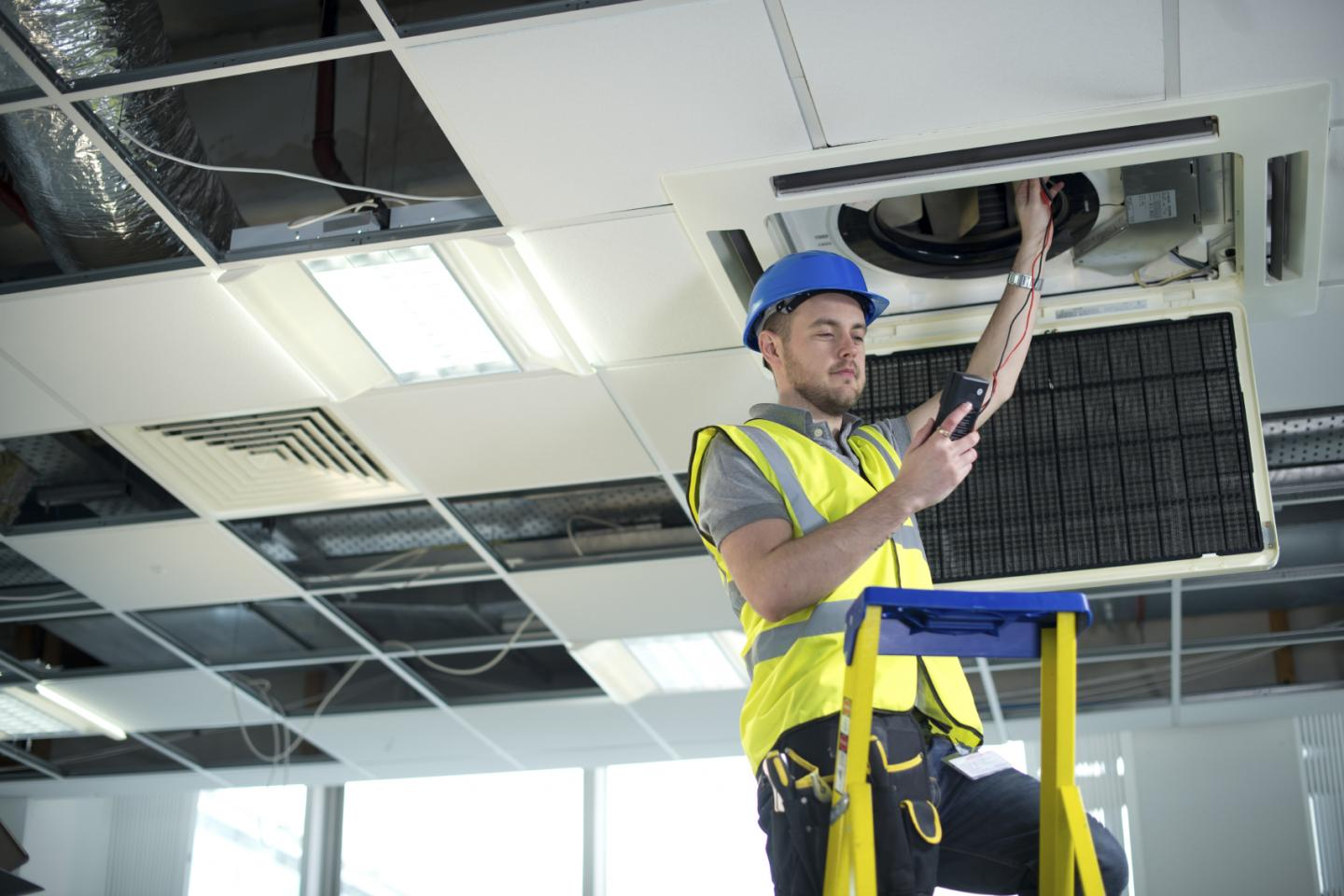 electrician fitting air conditioning to office interior